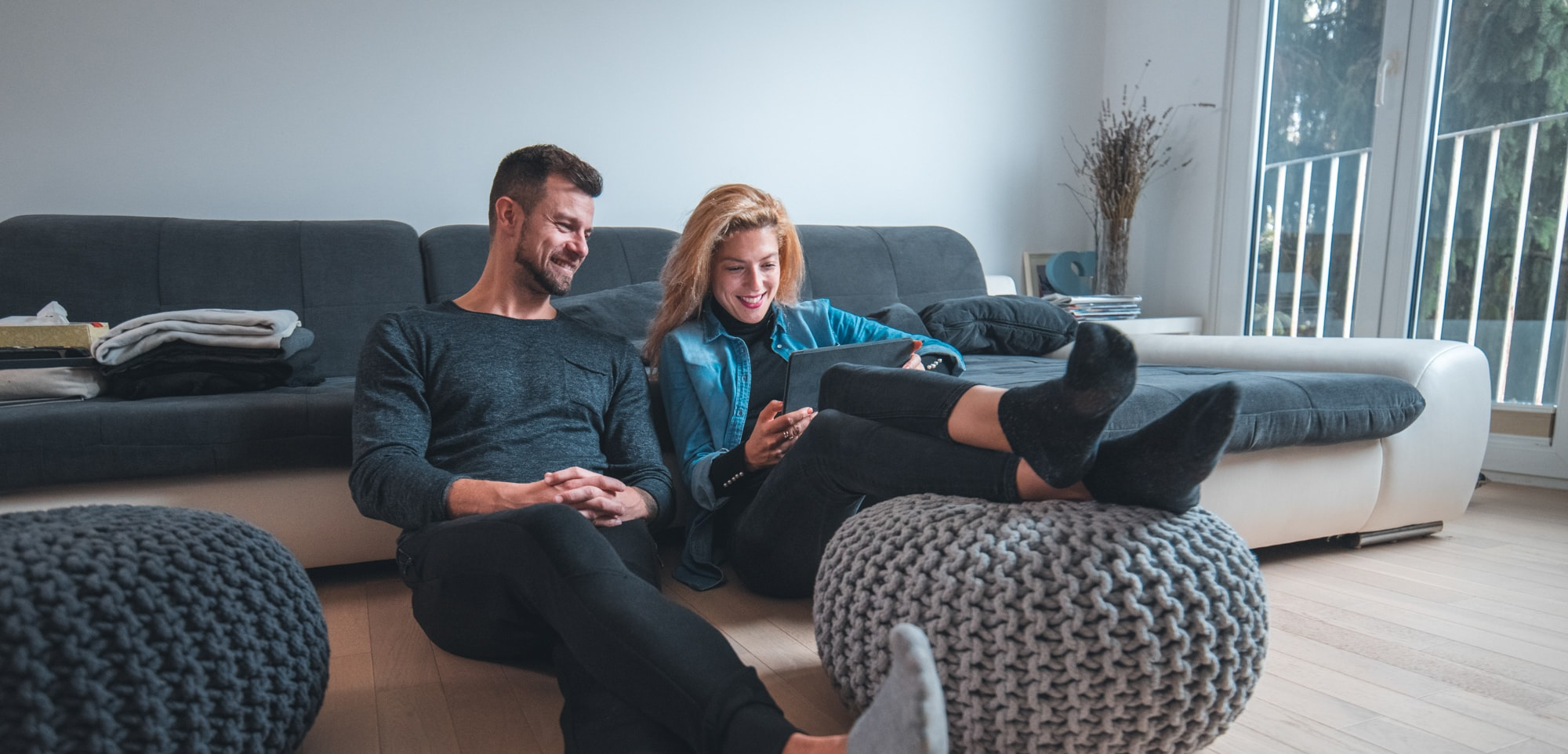 Couple sitting in living room while looking at tablet
